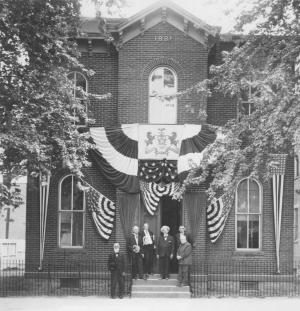 Photo of the Hamilton Library Building with group of men in front. Building decorated with bunting for the 1909 Old Home Week.