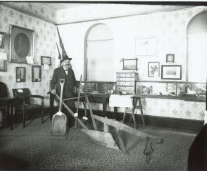 Photo of William E. Miller, Congressional Medal of Honor recipient and President of the Hamilton Library Association stands with museum exhibits in one of the rooms of the Hamilton Library (now CCHS).