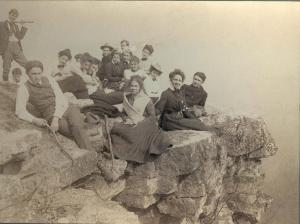 Photo of approximately seventeen young people sitting on rocks at Flat Rock, Doubling Gap, Pennsylvania.