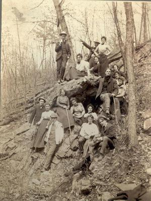 Photo of eighteen young people sitting and standing around Lewis Cave at Doubling Gap, Pa.