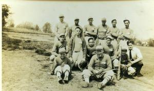 Photo of Posed  outdoor snapshot of  a baseball team with everyone in uniform except a man in white shirt and tie.