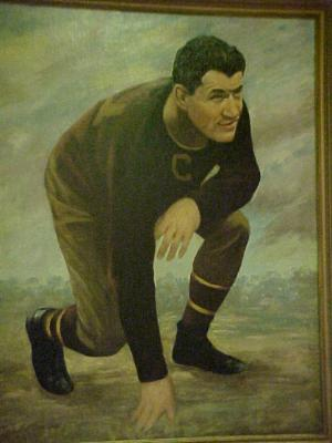 Photo of a framed oil portrait of Jim Thorpe in football uniform by Paul Bloser in 1959.