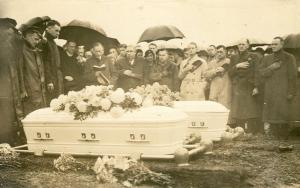 Outdoor B&W photo of a men and women standing around coffins in Westminster Cemetery near Carlisle, PA. Two coffins are visible, and a third is probably hidden behind one.