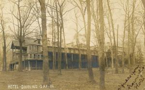 Divided back postcard with B&W outdoor photo of Doubling Gap Hotel among trees without leaves